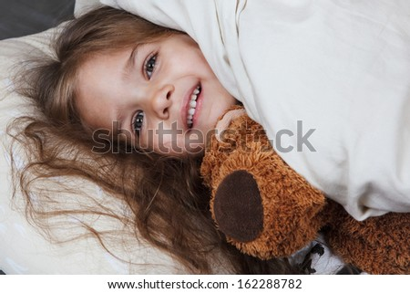 pretty little girl with toy in bed - stock photo