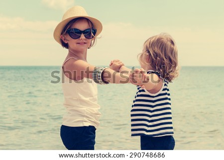 Pretty little girls (sisters) dancing on the beach. Selective focus. - stock photo