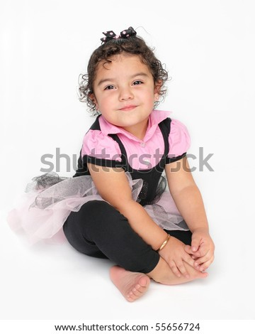pretty little Hispanic Mexican girl in pink tutu sitting on white background with big smile on her face - stock photo