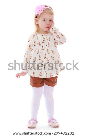 Pretty little white girl with a bow on her head and a colorful shirt and brown shorts stands in front of the camera while holding his head on his hand-Isolated on white background - stock photo