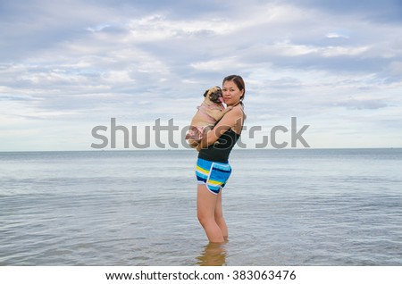 Pretty lonely asia girl hold a cute dog puppy pug against beach , sea and blue sky background and smile to camera. - stock photo