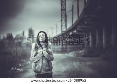 Pretty long hair brunette girl with old industrial bridge behind, black and white - stock photo