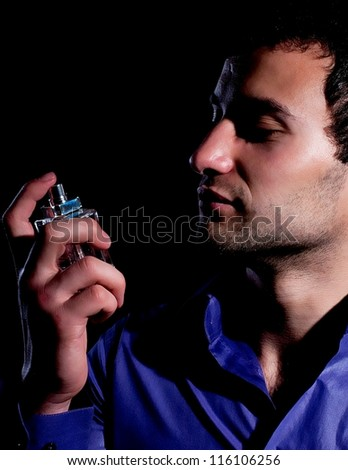 Pretty man with perfume bottles on black background - stock photo