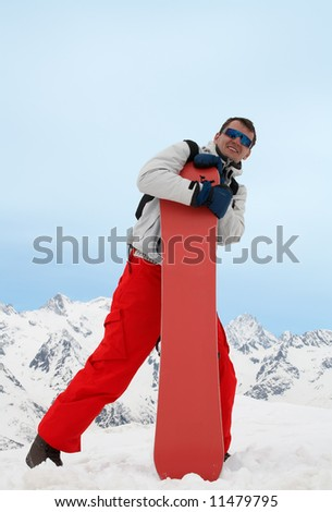 Pretty man with red snowboard in red pants - stock photo