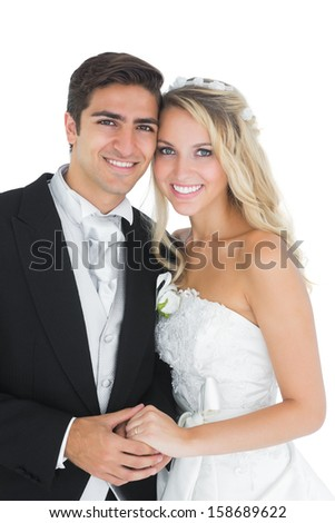 Pretty married couple posing holding hands smiling at camera - stock photo