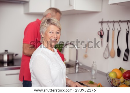 Pretty Matured Wife Smiling at the Camera while Preparing Something to Eat at the Kitchen with her Husband - stock photo