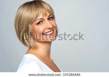 Pretty middle aged lady posing over grey background - stock photo