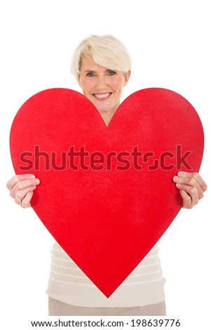 pretty middle aged woman presenting heart shape on white background - stock photo