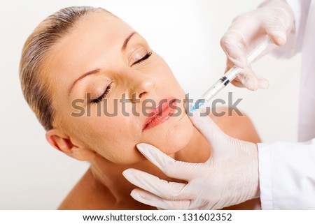 pretty middle aged woman receiving cosmetic injection on her chin