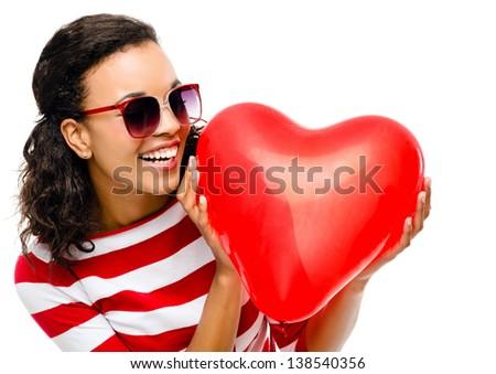 Pretty mixed race girl holding red heart balloon - stock photo