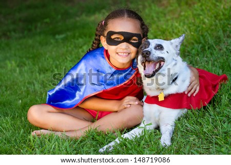 Pretty mixed race girl hugging her pet  with both dressed up in super hero costumes - stock photo