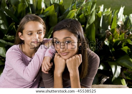 Pretty mixed-race Indian teen girl smiling with 10 year old sister leaning on shoulder - stock photo