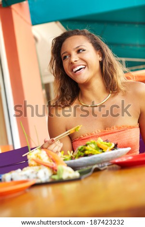Pretty Mixed Race Woman Enjoying A Meal At A Restaurant. African American female enjoying japanese cuisine at a fancy restaurant, using chopstick and really happy.