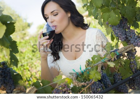 Pretty Mixed Race Young Adult Woman Enjoying A Glass of Wine in the Vineyard. - stock photo