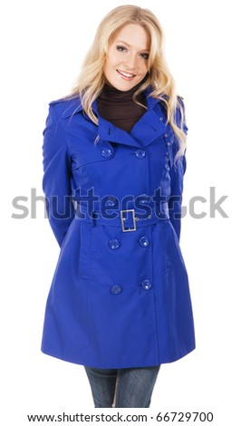 Pretty model in blue coat against white background - stock photo