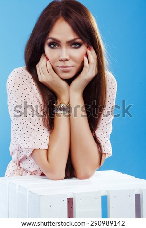 Pretty model with long straight hair posing on blue background. Young attractive Caucasian brunette girl wearing pink dress and some stylish accessories.  - stock photo