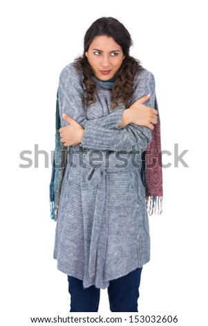 Pretty model with winter clothes being cold on white background