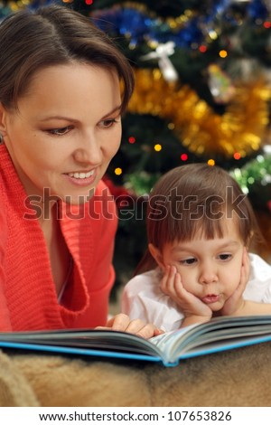 pretty mom reading with her little daughter