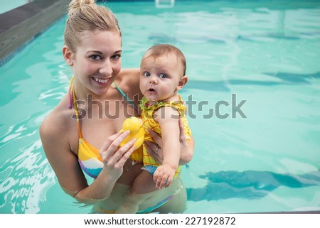 Pretty mother and baby at the swimming pool at the leisure center - stock photo