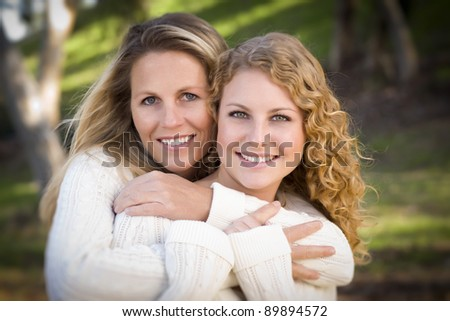 Pretty Mother and Daughter Portrait Hugging in the Park on a Fall Day. - stock photo
