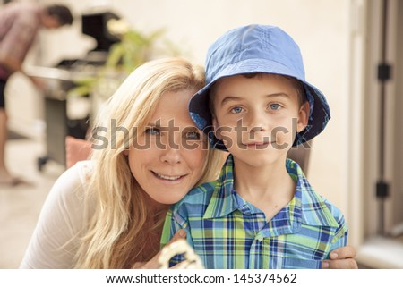 Pretty Mother and young son posing for a picture while dad BBq's in the background - stock photo