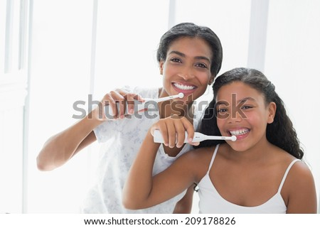 Pretty mother brushing her teeth with her daughter at home in bathroom - stock photo