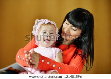 pretty mother playing with her baby - stock photo