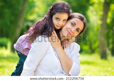 Pretty mother with her daughter at summer park - stock photo