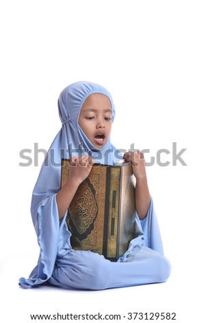 Pretty Muslim Girl Reading Holy Book of Quran Isolated on White Background - stock photo