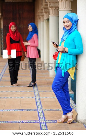 Pretty Muslim girl standing with holding smartphone - stock photo