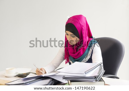 Pretty Muslim woman busy at office - stock photo