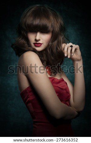 Pretty, mysterious, gorgeous woman with smooth brown hair with straight fringe wearing red, satin top, big old necklace and red lipstick, her eyes are in shadow. - stock photo