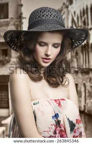 Pretty, natural, cheerful model with brown, curly hair. She is wearing summer hat and dress with flower pattern. - stock photo