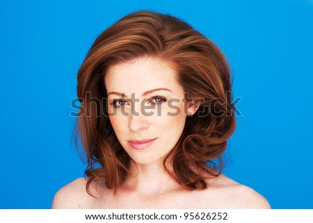 Pretty natural redhead woman with blue eyes and subtle makeup facing camera. - stock photo