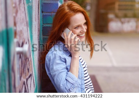 Pretty natural young woman chatting on a mobile phone with a smile as she leans back relaxing against an old exterior urban brick wall