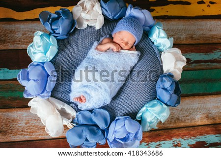 Pretty newborn baby on the blue bed