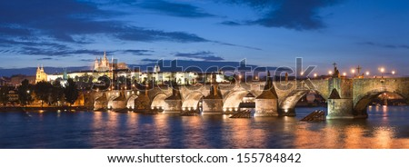 Pretty night time illuminations of Prague Castle, Charles Bridge and St Vitus Cathedral reflected in the Vltava river running through the heart of the city of Prague in the Czech Republic. - stock photo