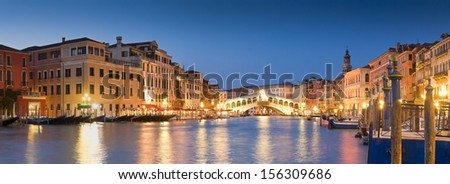 Pretty night time illuminations of the iconic Rialto Bridge (1591) and Venetian Villas over the grand canal in Venice. Stitched panoramic image. - stock photo