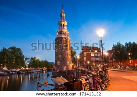 Pretty night time illuminations of the Montlebaanstoren Tower (1512) overlooking Oosterdk in central Amsterdam.