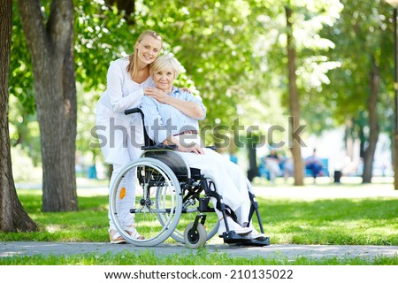Pretty nurse taking care of senior patient in a wheelchair - stock photo