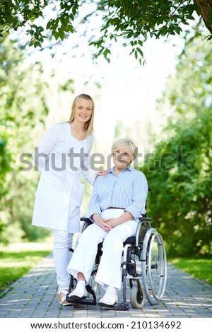 Pretty nurse taking care of senior patient while taking walk in park - stock photo