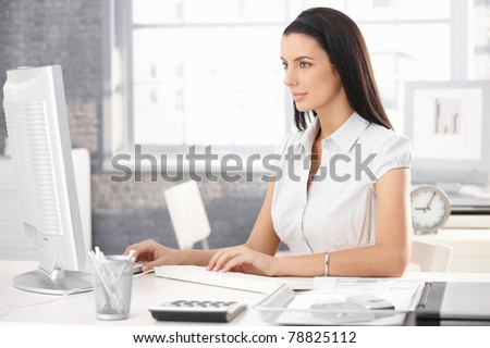 Pretty office worker girl sitting at desk in office, using desktop computer.? - stock photo