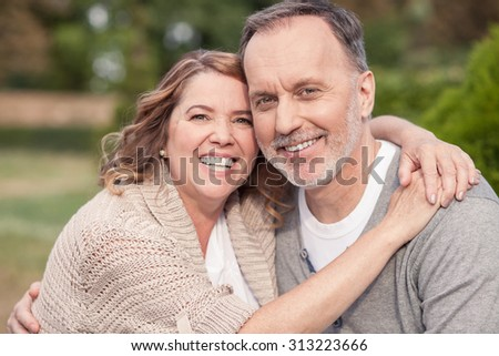 Pretty old husband and wife are sitting in park. They are embracing and smiling. The man and woman are looking at the camera with happiness - stock photo