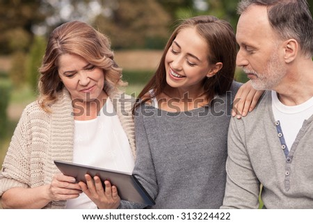 Pretty old married couple and their young daughter are using a tablet. They are looking at it with interest and smiling. They are sitting in park and embracing with love - stock photo