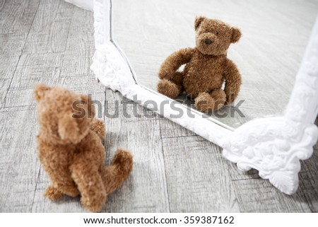 Pretty old vintage  Teddy Bear toy looking at the mirror  - stock photo
