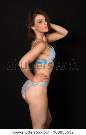 Pretty petite brunette in pale blue lingerie - stock photo