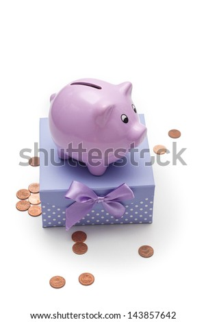 Pretty piggy Bank stands on a gift box with bow, isolated on white background