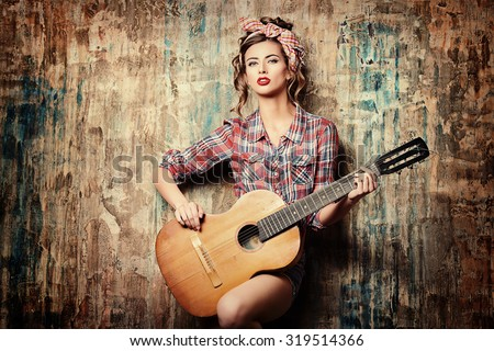 Pretty pin-up girl posing with guitar. Beauty, fashion. - stock photo