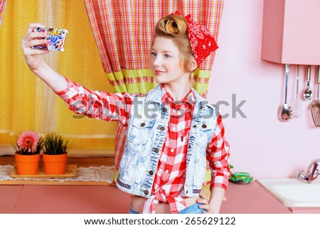 Pretty pin-up girl teenager taking picture of herself on a pink kitchen. Beauty, youth fashion. Pin-up style. Selfie. - stock photo