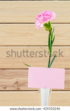 Pretty Pink Carnation Flowers on White Vase with Blank Greeting Card on Wooden Table. - stock photo